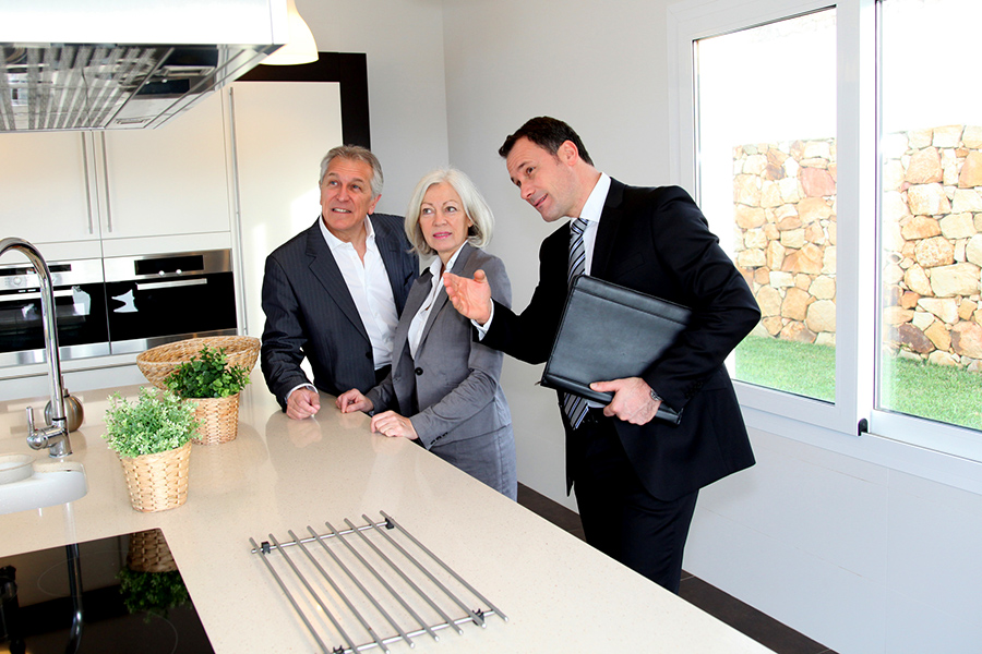 Real-estate agent showing interior of house to senior couple before home inspection services are scheduled