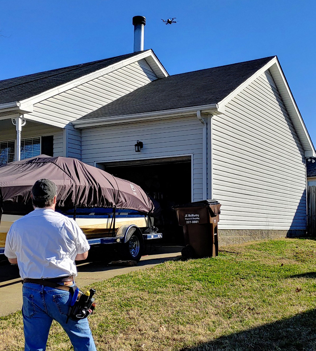 Jim Fuson flying an aerial drone over a house while preforming home inspection services