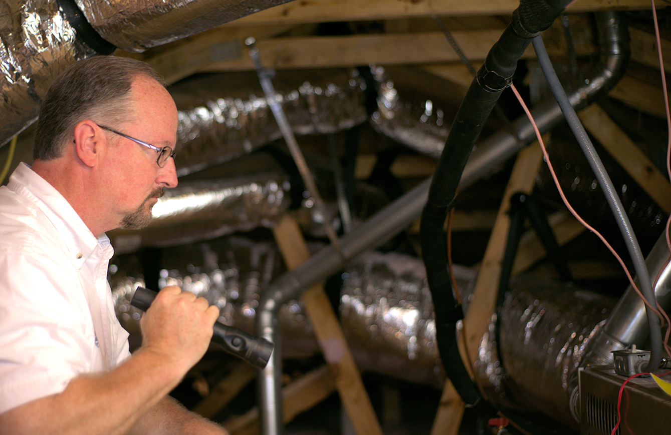 Jim Fuson doing a home inspection in an attic