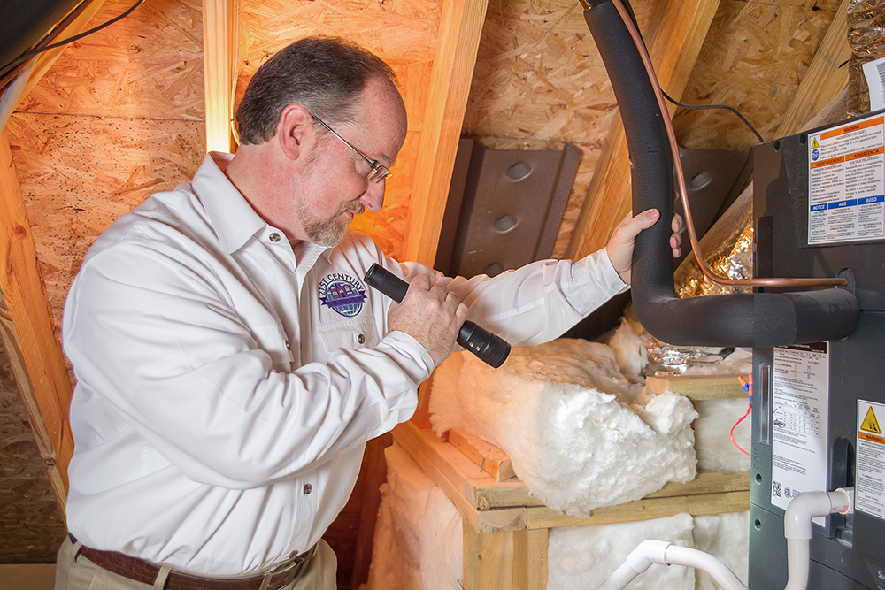 Jim preforming home inspection services in the attic of a house