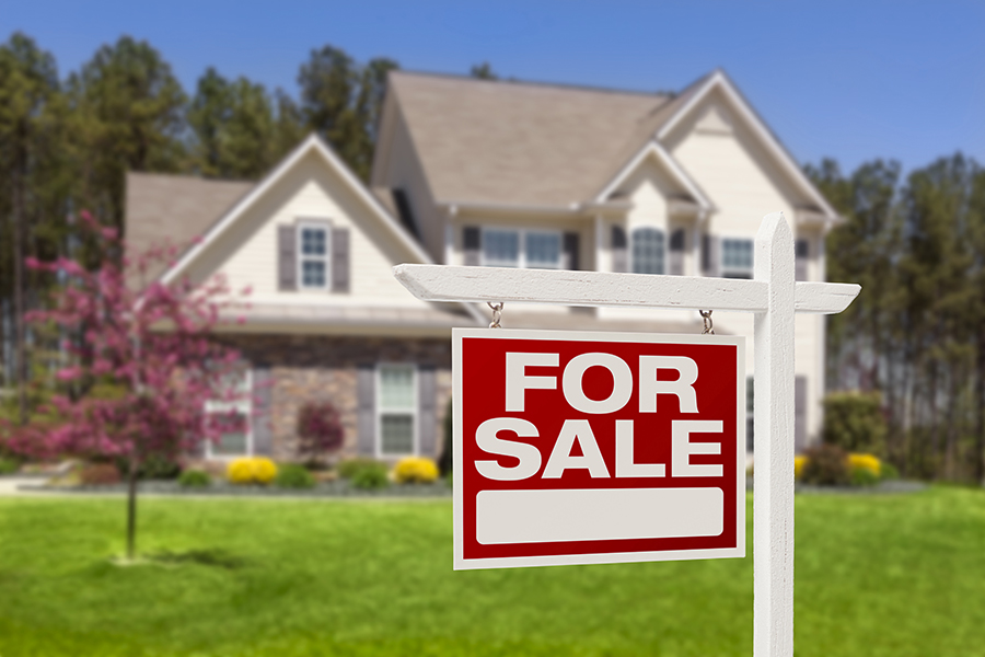 Home For Sale Real Estate Sign in front of a new construction house seen while preforming home inspection services