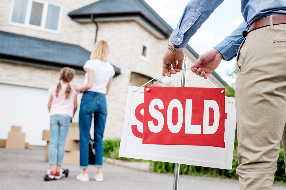 realtor putting a sold sign in front of a a house bought by a mom after a thorough home inspection