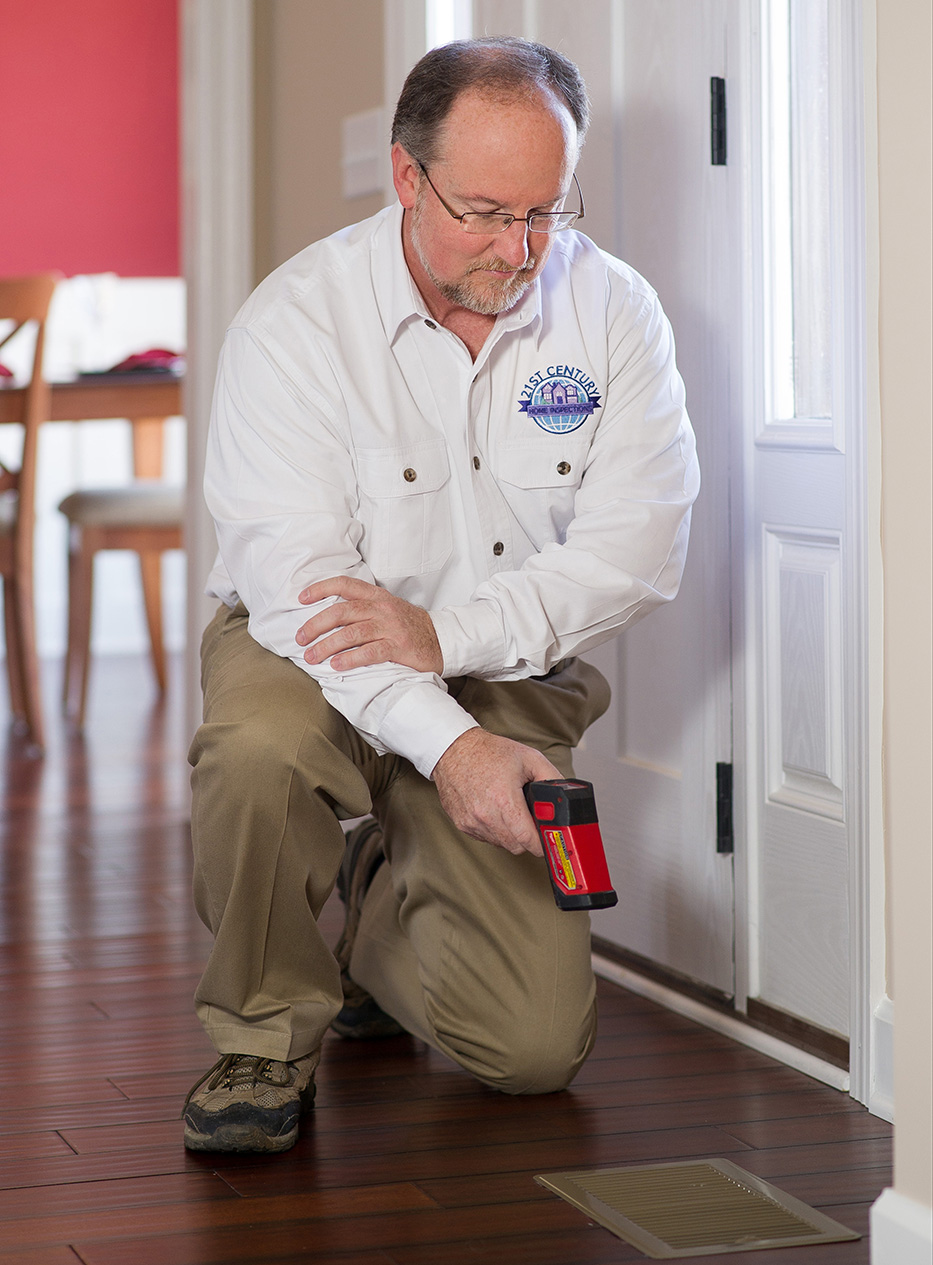 Jim, one of our certified home inspectors, using a laser thermometer inside of a house