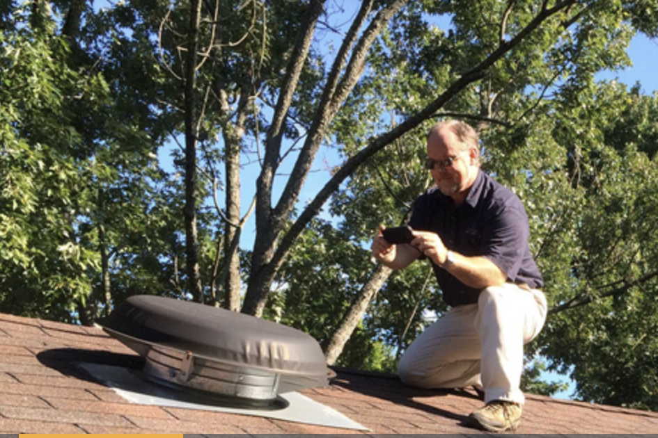 Jim Fuson on the roof of a house preforming home inspection services